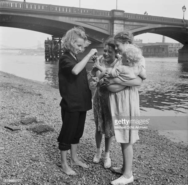 British actress Joan Greenwood standing with two young fans, one of which holds a baby, on the shingle of the Thames riverbank, beneath Battersea...