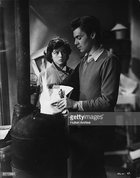 British actress Joan Rice , who began her career as a waitress, watches actor Dirk Bogarde burn some of his paintings in the stove in a scene from...