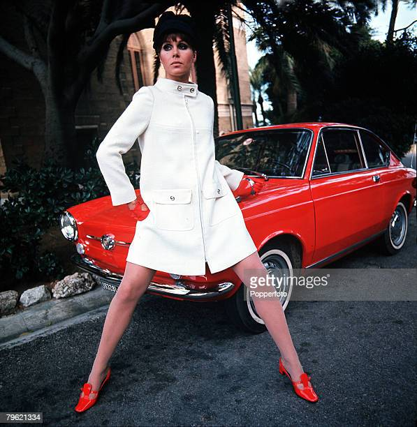 British actress Joanna Lumley poses by a red Fiat 850 Coupé as she models a white coat worn with red shoes and matching gloves 1968