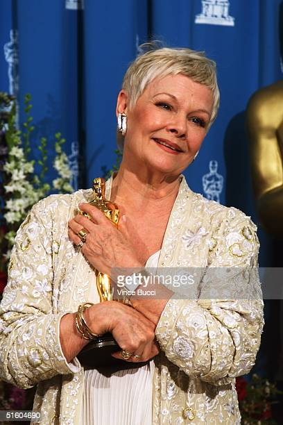 British actress Judi Dench cradles her Oscar for Best Supporting Actress for her role in Shakespeare in Love at the 71st Annual Academy Awards in Los...