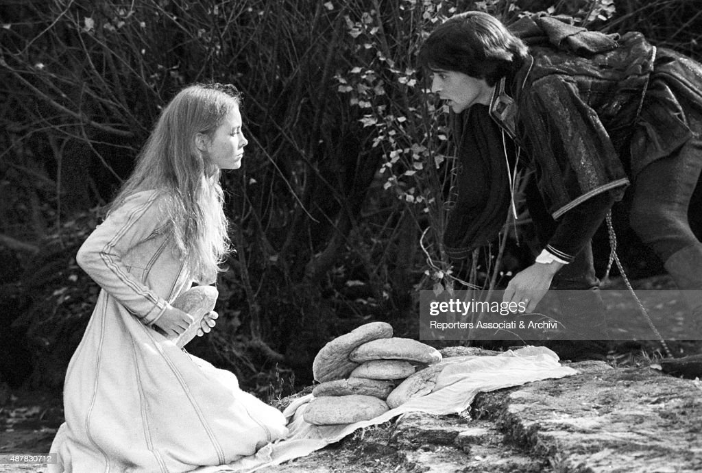 British actress Judy Bowker kneeling with some bread in front of