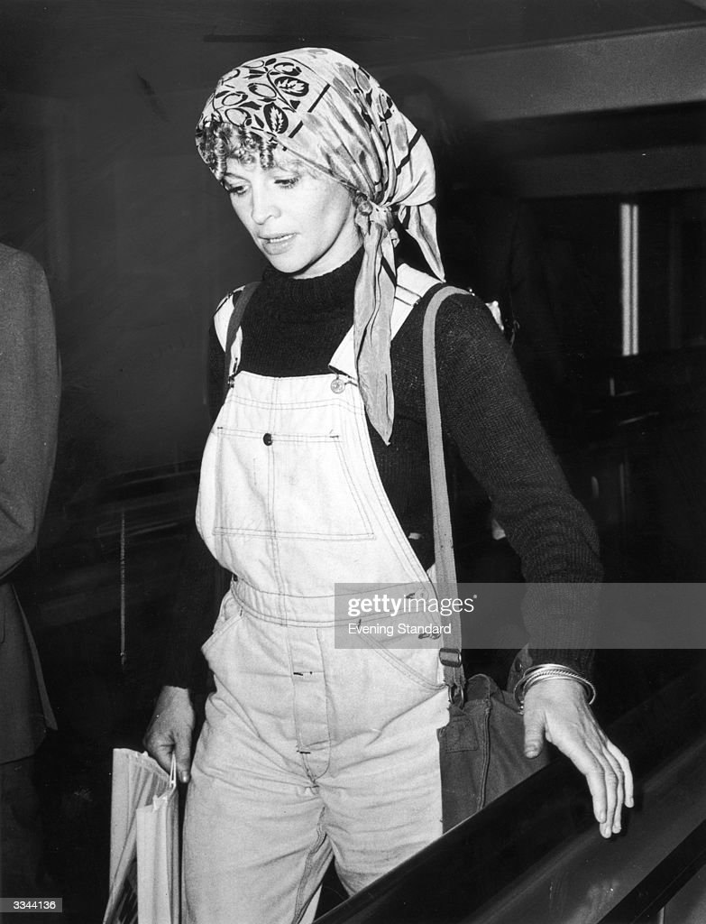British actress Julie Christie arrives at Heathrow Airport wearing a pair of dungarees and a headscarf, October 1973.