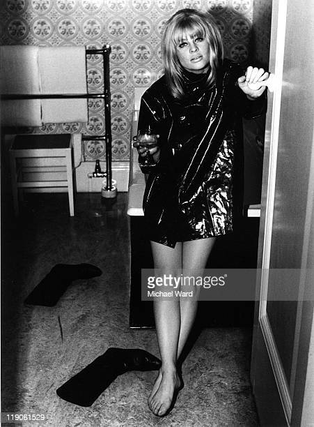 British actress Julie Christie barefoot wearing a black PVC jacket 1963