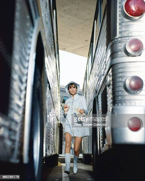 British actress Julie Christie walks between a pair of parked buses in a scene from 'Petulia' California 1968