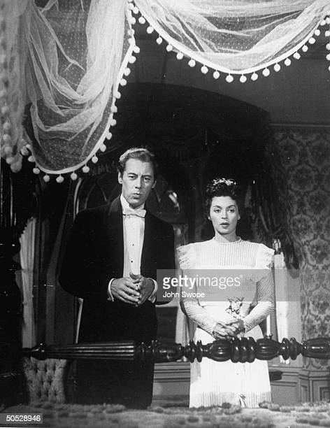 British actress Lilli Palmer standing with her husband, Rex Harrison, in the screenplay The Fourposter.