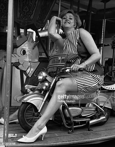 British actress Liz Fraser has a ride on a merrygoround at the Battersea Fun Fair London 1966