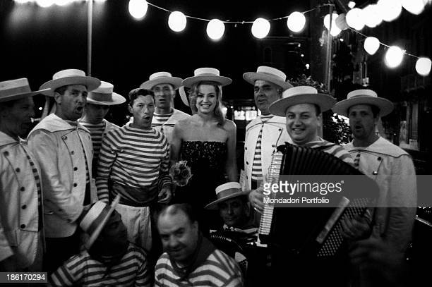 British actress Margaret Lee smiling with some gondoliers Venice 1966