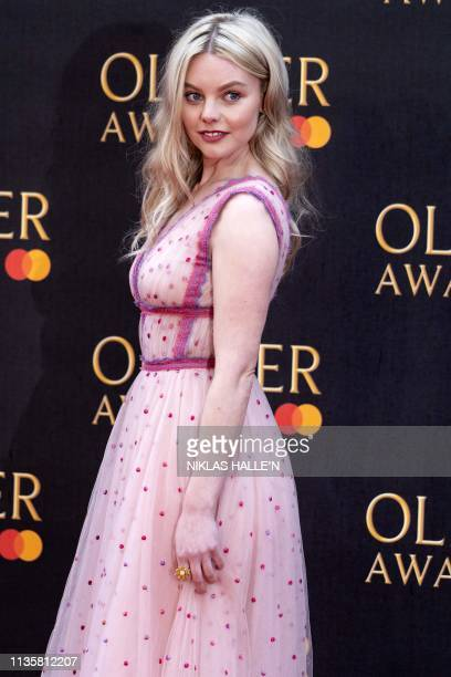 British actress Nell Hudson poses on the red carpet upon arrival to attend The Olivier Awards at the Royal Albert Hall in central London on April 7...