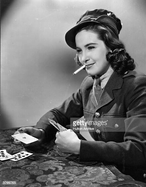 British actress Patricia Roc plays her hand in a scene from the film 'Pack Up Your Troubles' directed by Oswald Mitchell for 20th Century Fox