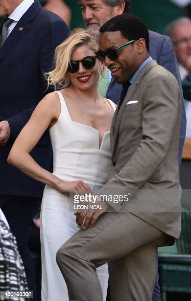 British actress Sienna Miller and British actor Chiwetel Ejiofor arrive on Center Court ahead of the men's semifinal match between Serbia's Novak...