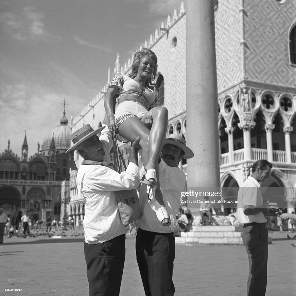 British actress Stephanie Beacham lifted by gondoliers in St. Mark Square, Venice, 1971.