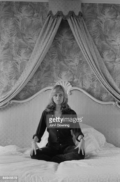 British actress Susan George sits crosslegged on a large bed 26th February 1978