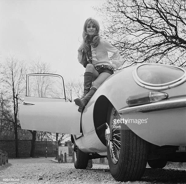 British actress Suzy Kendall sitting on a Jaguar Etype sports car 11th April 1969