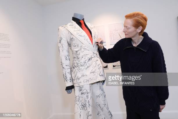 British actress Tilda Swinton adds her signature to the suit of British costume designer Sandy Powell before it goes up for auction at Phillips...