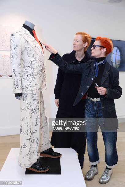 British actress Tilda Swinton and British costume designer Sandy Powell pose with Sandy Powell's suit before it goes up for auction at Phillips...