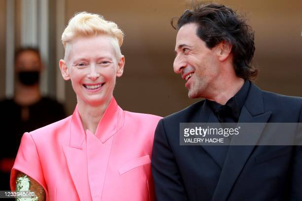 """British actress Tilda Swinton and Us actor Adrien Brody smile as they arrive for the screening of the film """"The French Dispatch"""" at the 74th edition..."""
