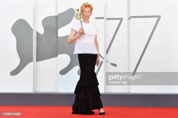 """British actress Tilda Swinton arrives for the opening ceremony and the screening of the film """"Lacci"""" on the opening day of the 77th Venice Film..."""