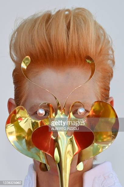 """British actress Tilda Swinton holds a golden masquerade mask as she arrives for the screening of the film """"The Human Voice"""" presented out of..."""