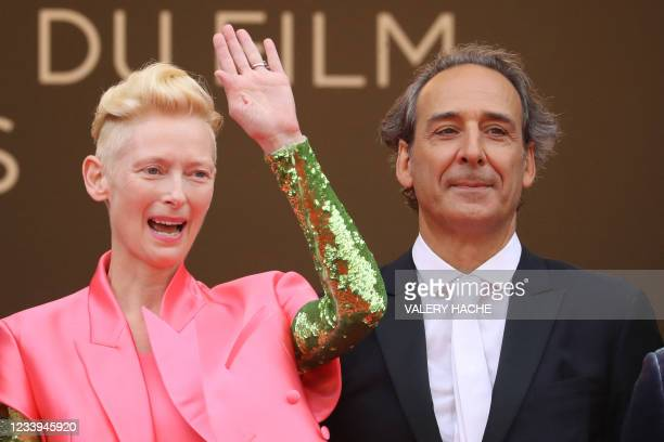 """British actress Tilda Swinton waves as she arrives with French music composer Alexandre Desplat for the screening of the film """"The French Dispatch""""..."""