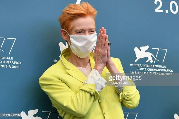"British actress Tilda Swinton, wearing a face mask, acknowledges photographers during a photocall for the film ""The Human Voice"" presented out of..."