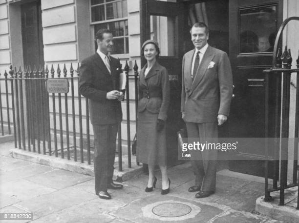 British actress Vivien Leigh and her husband, actor Laurence Olivier with playwright Terence Rattigan outside the Theatre Royal in London, 1953. They...