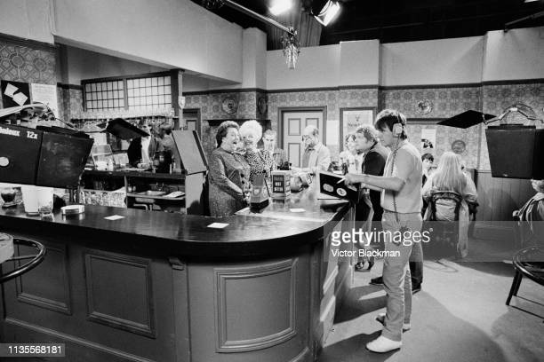 British actresses Betty Driver and Julie Goodyear with crew member and extras in the 'Rovers Return' pub on the set of British soap opera Coronation...