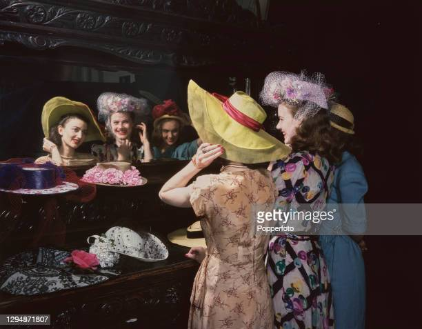 British actresses, from left, Zena Marshall, Josephine Stuart and Susan Shore try on hats by Beresford, Berkeley and Otto Lucas respectively, in...