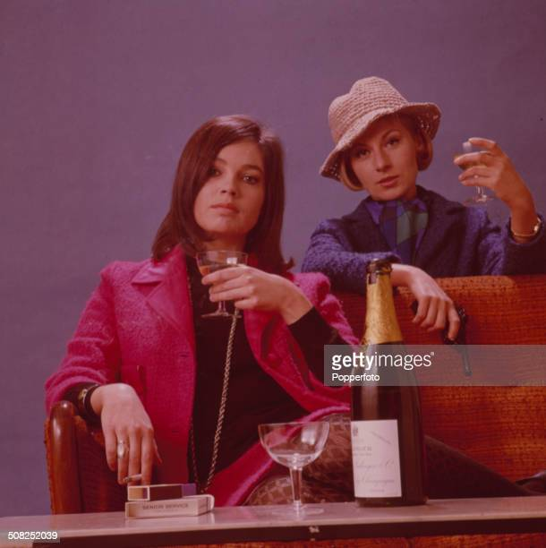British actresses Kathleen Breck and Ann Lynn posed together with a bottle of sparkling wine on the set of the television drama series 'Danger Man'...