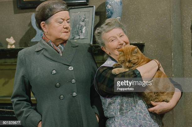 British actresses Violet Carson as 'Ena Sharples' and Margot Bryant as 'Minnie Caldwell' holding a cat pictured together in a scene from the...