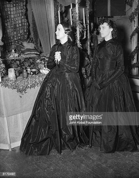 British actresses Vivien Leigh and Olivia de Havilland in costume for their roles in the American civil war epic 'Gone With the Wind'