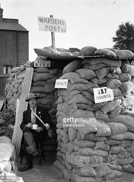 A British air raid warden relaxes outside an air raid shelter in 1939