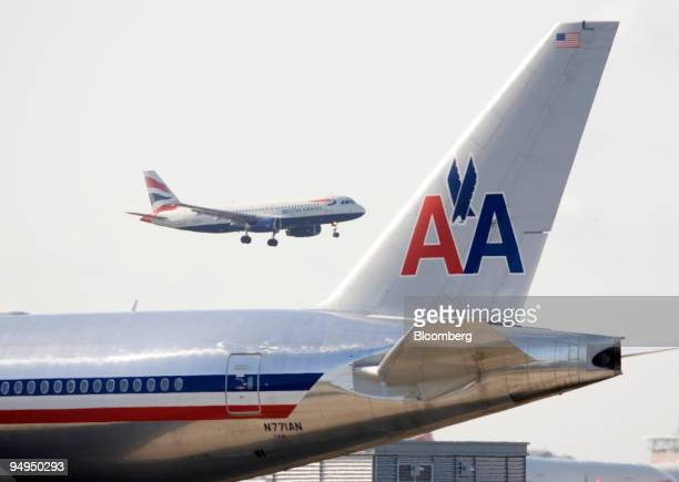 British Airways aeroplane prepares to land as an American Airlines aeroplane waits on the runway at Heathrow airport in London UK on Friday May 22...