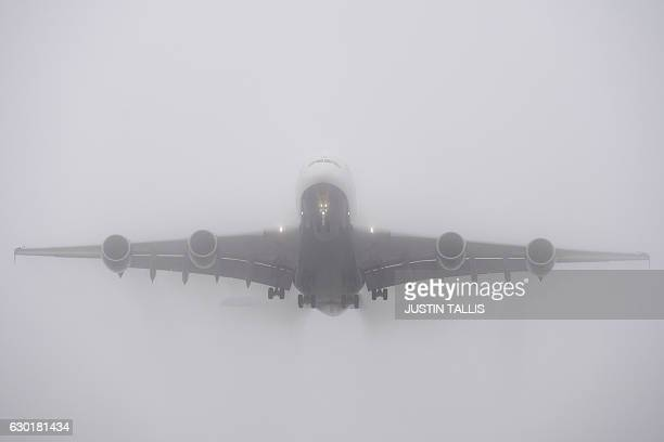 A British Airways Airbus A380 is shrouded in fog as it comes in to land at Heathrow Airport in west London on December 18 2016 The Met Office issued...
