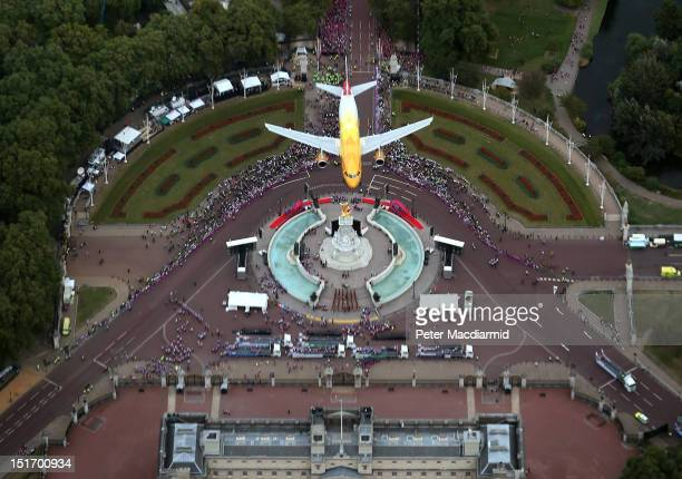 British Airways Airbus aircraft flies over the Queen Victoria Memorial at Buckingham Palace during the London 2012 Victory Parade for Team GB and...