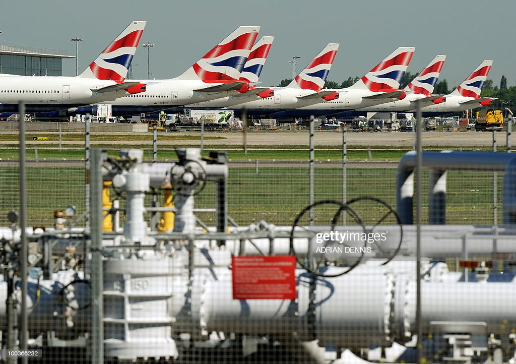 British Airways aircraft are pictured parked behind a fuel storage depot at Heathrow Airport, west of London, on May 24, 2010. Thousands of air travellers faced renewed travel chaos on Monday as British Airways cabin crew launched a five-day strike, after last-ditch negotiations collapsed. AFP PHOTO/Adrian Dennis