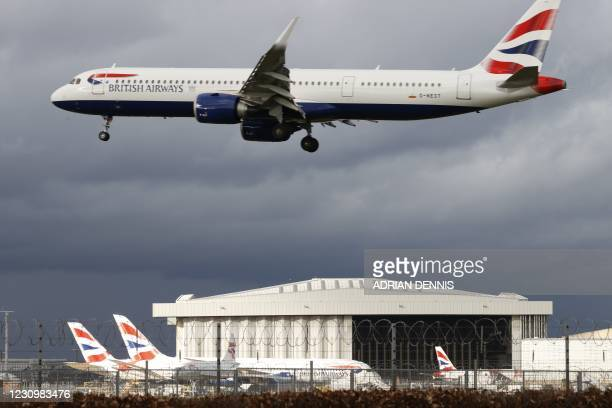 British Airways aircraft flies over parked British Airways planes on the tarmac at London Heathrow Airport in west London on February 5, 2021. -...
