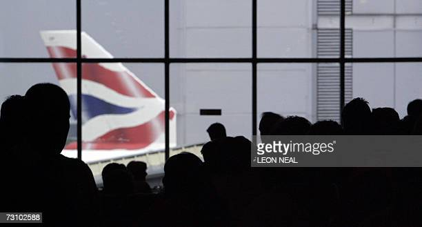 A British Airways aircraft is pictured as passengers queue at London's Heathrow airport in southeast England 14 August 2006 British Airways announced...