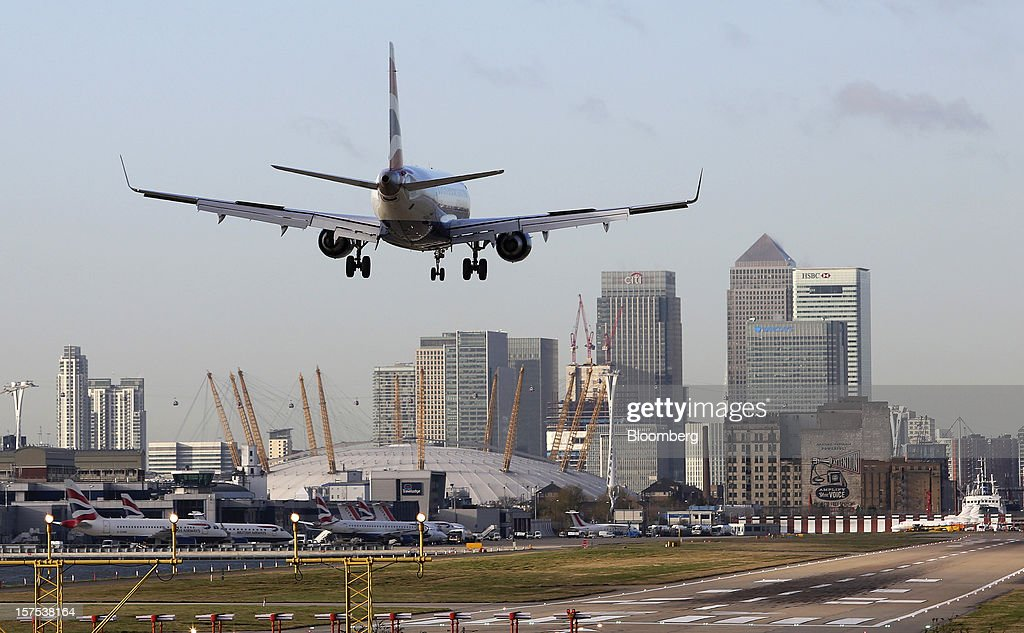 A British Airways aircraft lands at City Airport against a backdrop of the Canary Wharf financial district in London, U.K., on Tuesday, Dec. 4, 2012. Air France-KLM Group's CityJet unit is studying options for a new investor, with a trade buyer a possibility given its strength at London City airport, Chief Executive Officer Christine Ourmieres said in an interview. Photographer: Chris Ratcliffe/Bloomberg via Getty Images