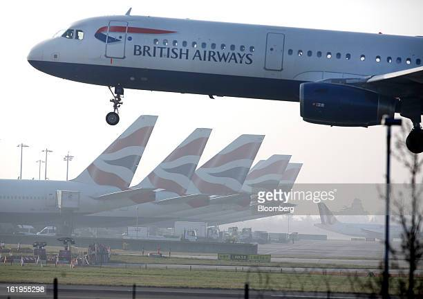 A British Airways aircraft lands at London Heathrow airport against a backdrop of British Airways branded tailfins on aircraft near terminal 5 in...