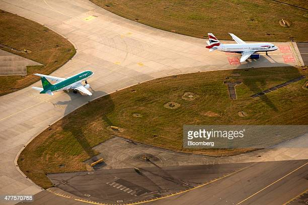 A British Airways aircraft operated by British Airways Plc right and an Aer Lingus aircraft operated by Aer Lingus Group Plc prepare to takeoff from...