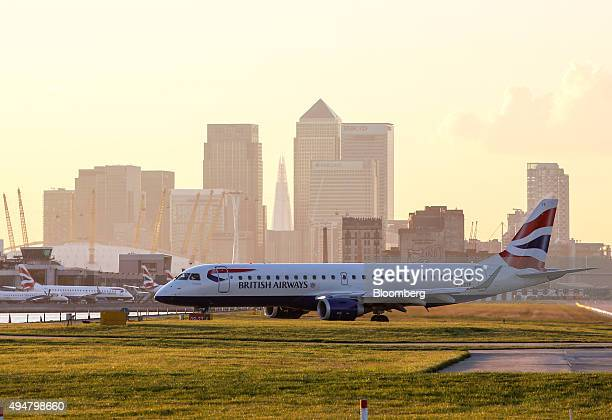 A British Airways aircraft operated by British Airways Plc taxis along the tarmac at London City Airport near to the Canary Wharf business financial...