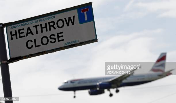 A British airways aircraft prepares to land at London Heathrow airport beyond the village of Longford in west London on June 8 2018 Britain's...
