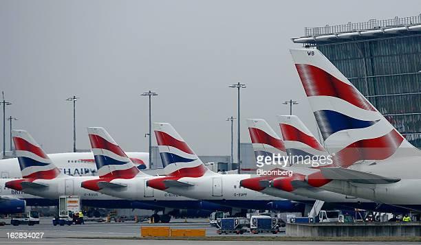 British Airways aircraft stand at departure gates at Terminal 5 at Heathrow Airport in London UK on Thursday Feb 28 2013 British Airways parent...