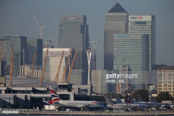 British Airways airplanes are seen on the runway with the towers and buildings of the Canary Wharf financial district in background before taking off...