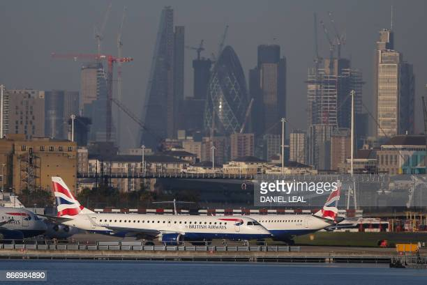 British Airways airplanes taxi on the runway with the financial towers and office buildings of the City of London in background before taking off at...