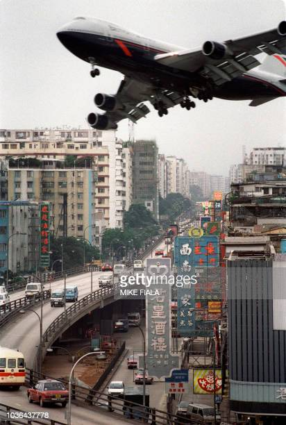 A British Airways Boeing 747 jetliner banks 17 April 1990 over Prince Edward Road in Hong Kong on approach of Kai Tak internatioanl airport People of...
