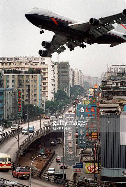 A British Airways Boeing 747 jetliner banks 17 April 1990 over Prince Edward Road in Hong Kong on approach of Kai Tak internatioanl airport People of...