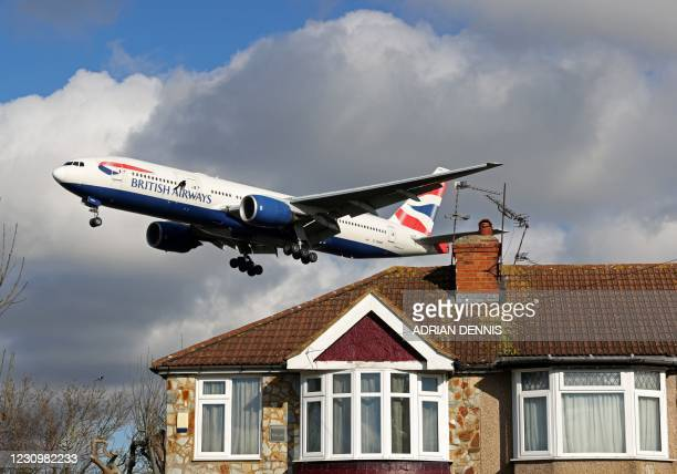 British Airways Boeing 777-236 aircraft flies over residential houses as it prepares to land at London Heathrow Airport in west London on February 5,...
