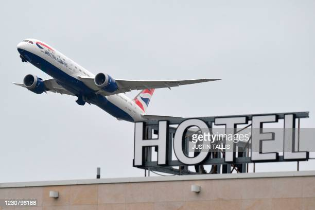 British Airways Boeing 787 Dreamliner airplane is seen flying over a hotel at Heathrow Airport in west London on January 26, 2021. - The British...