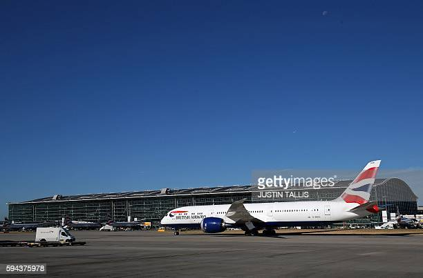 A British Airways Boeing 7879 Dreamliner aircraft taxis past Terminal 5 towards the runway at London's Heathrow Airport on August 23 2016 / AFP /...